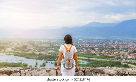 Travel Albania - back view of young woman in a white dress standing near a stone wall of castle Rozafa and looking over the valley of river Drin. There is city Shkoder on the right side of the river