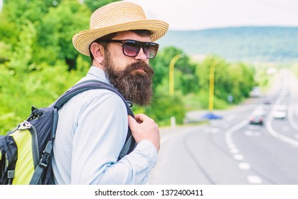 Travel alone. Hitchhiking means transportation gained asking strangers for ride in their car. Hitchhiker travel alone try stop transport to get to destination. Man at edge of highway wait transport.