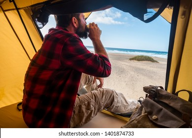 Travel and alternative hotel room destination concept with people lonely man drinking a coffee inside a tent in free camping at the beach for different lifestyle holiday vacation - enjoying freedom