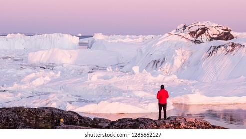 Travel in arctic landscape nature with icebergs - Greenland tourist man explorer - tourist person looking at amazing view of Greenland icefjord - aerial drone image. Man by ice and iceberg, Ilulissat.