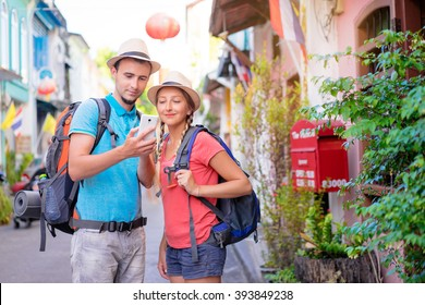Travel Asia. Young couple looking at phone travelling Asia.