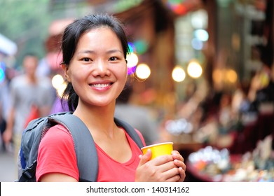 travel asian woman with a cup of coffee smile at street
