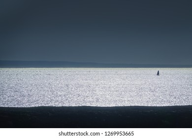 travel background in backlight with silhouette of a lonely sailboat on a reflecting ocean, Lanzarote, canary islands, Spain, Europe