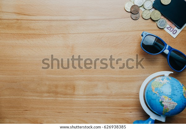 Travel background with coins, cards, mobile phone, globe and coffee. top view empty space for text