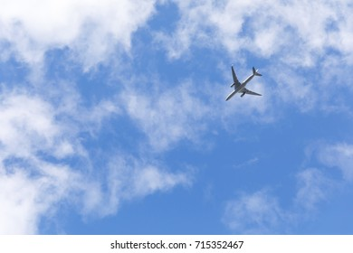 Travel background of a commercial plane flies in the sky toward blue sky