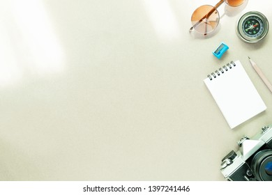 Travel background concept. Camera, sunglasses, notepad and compass on table with free space for text.
