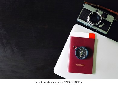 Travel background concept. Passport, compass, camera and laptop on black table with free space for text.