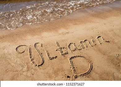 travel background with waves of sea, beach and word vitamin D written in sand