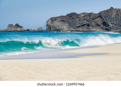 travel background with a white lonely beach, turquoise atlantic ocean and a rocky volcanic coastline, Lanzarote, canary islands, spain, europe