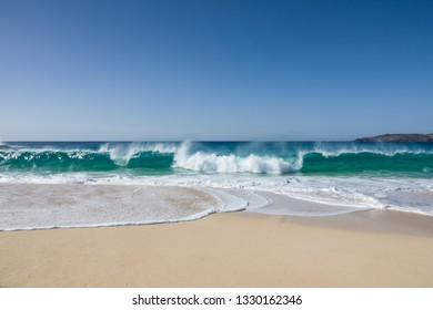 travel background with white sand of a beautiful beach and  waves of a turquoise sea under a blue sky
