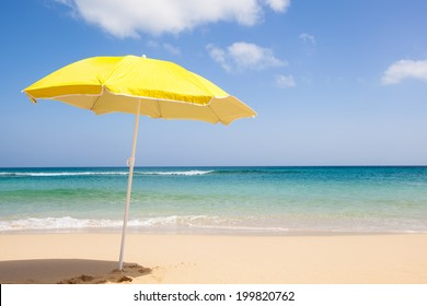 travel background with a yellow sunshade, blue sky, turquoise sea and a beautiful beach, Fuerteventura, Canary Islands, Spain, Europe