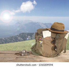 travel backpack with hat over wooden table