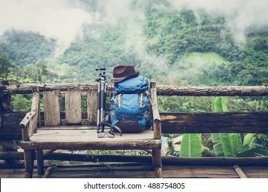 Travel backpack on the wooden bench with landscape view of mountain and fog
