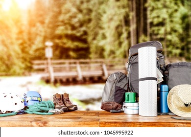 Travel backpack on wooden desk space and landscape of forest with river.