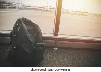 Travel bag in airport departure lounge, airplane in background, summer vacation concept, traveler suitcases in airport terminal waiting area, empty hall interior with large windows, focus on bag
