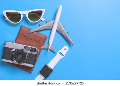 Travel blogger accessories on blue copy space