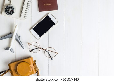 Travel Blogger accessories on white wood copy space
