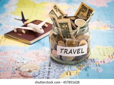 旅行预算概念. 在世界地图上有罗盘、护照和飞机玩具的玻璃罐中节省旅行资金