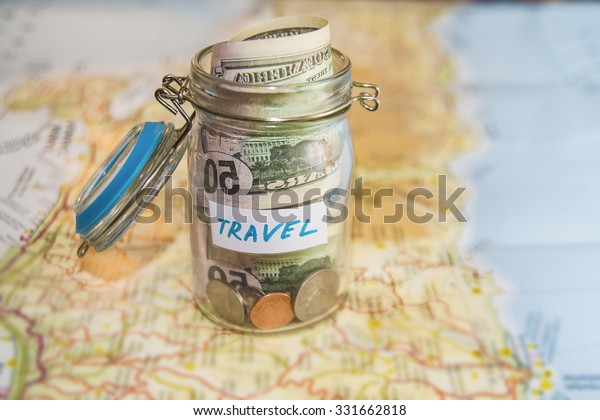 Travel budget - vacation money savings in a glass jar on world map. Collecting money for travel. Glass tin as moneybox with cash savings (banknotes and coins) on table and map as background.