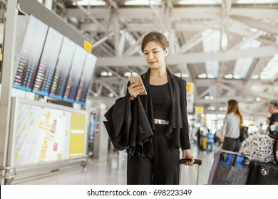 Travel, Business, Advertise concept - Everything looks great. Beautiful Asian businesswoman using smartphone checking her flight or online check-in at airport, with luggage. Air travel.