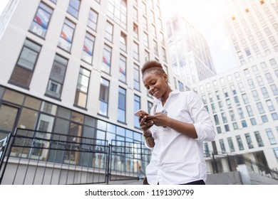 travel, business trip, people and technology concept - happy young african american woman in white basic shirt walking down city street and calling on smartphone. Low angle summer outdoor shot.