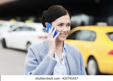 travel, business trip, people and tourism concept - smiling young woman calling and talking on smartphone over taxi station or city street