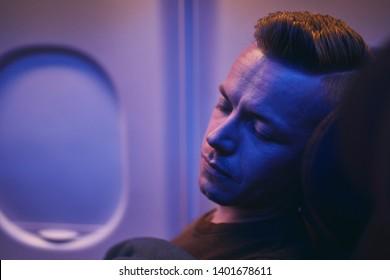 Travel by airplane. Man sleeping during night flight.