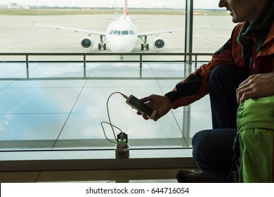 Travel by airplane. Passenger charging mobile device at the lounge of airport terminal. Silhouette of a man with phone and wire.