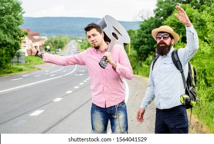 Travel by autostop. Hopeless hitchhiker. Company friends looking for transport. Men try stop car. Travelers with backpack and guitar ready strat new journey. Hitchhiker meet friend at road.