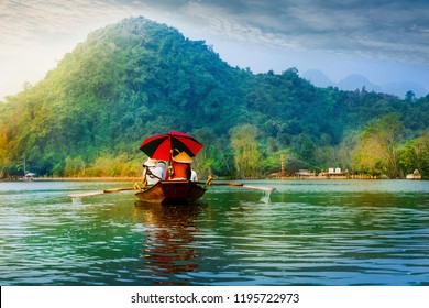 Travel by boat in flooded areas submerged trees in YEN stream, Myduc, Hanoi, Vietnam.