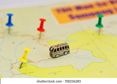 Travel by bus concept with geographical roadmap - close-up capture with different pushpins and tiny bus figurine. Macro capture with small depth of field. No cities or other objects names.