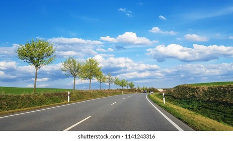Travel by car in Germany, long road in summer with green young trees along road, bright blue sky with clouds and beautiful european nature