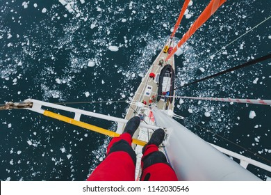 travel by sailing boat in Antarctica, extreme dangerous selfie, person feet standing on mast of a yacht with floating ice, scary top view, adventure photographer