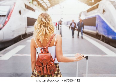 travel by train, woman passenger with suitcase waiting in railway station