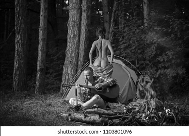 Travel, camping, couple, people, tent, fire, flag, tourist. Black and white photo. Sensual. Camping day. Holidays. Man and woman posing nature. Fashion. Model. Passionate concept. Passion. Fire.