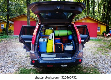 Travel car and camping luggage packed in the full car trunk. Outdoor wanderlust items. Outdoor, adventures and travel suv. Ready to go concept. Expedition, exploring swag and storage.