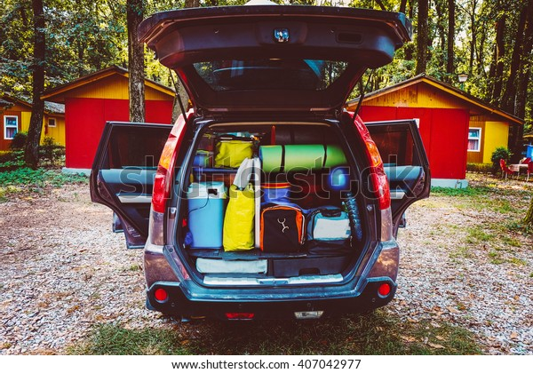 Travel car and camping luggage packed in the full car trunk. Outdoor wanderlust items. Outdoor, adventures and travel suv. Ready to go concept. Vintage hipster tone. Camping exploring.
