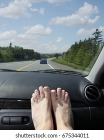 travel in the car on vacation, holiday, or road trip with feet on the dashboard and blue skies ahead in summer