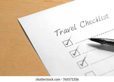 Travel checklist paper with red pen marking on tick box.
