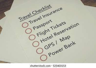 travel checklist printed on white paper over wooden floor. vantage color tone effect