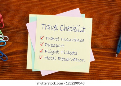 Travel Checklist text on note with pen on the wooden table.