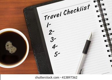 Travel Checklist word on a notebook with a pen and a cup of coffee