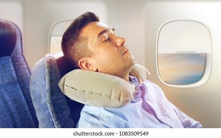 travel, comfort and people concept - man sleeping in plane with inflatable cervical neck pillow over porthole background