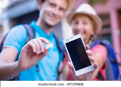 Travel and communication. Young couple of travelers showing sim-card and screen of smartphone. Focus on hands.