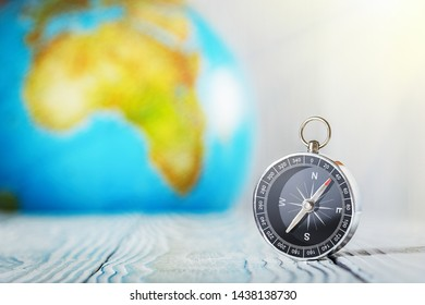 Travel compass and earth globus on wooden background. Journey, adventure lifestyle.Road to home.Trip.