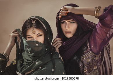 Travel concept. Adventure of two sisters princesses in the desert. Two girls have got to a sandstorm during journey. Creative art fashion portrait shot of two gorgeous attractive models with luxury