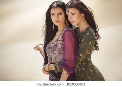 Travel concept. Adventure of two sisters serious princesses standing in the desert and looking at landscape. Two beautiful mixed race asian caucasianl girls enjoy a joint journey. Creative art fashion