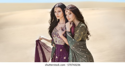 Travel concept. Adventure of two sisters princesses happy standing in the desert and looking at landscape. Two beautiful mixed race asian caucasianl girls enjoy a joint journey. Creative art fashion