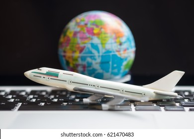 travel Concept. Airplane model toy on laptop computer with mini world ball as background.
