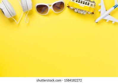 Travel concept backdrop with airplane, sunglasses, headphones and tram toy. Top view flat lay with copy space